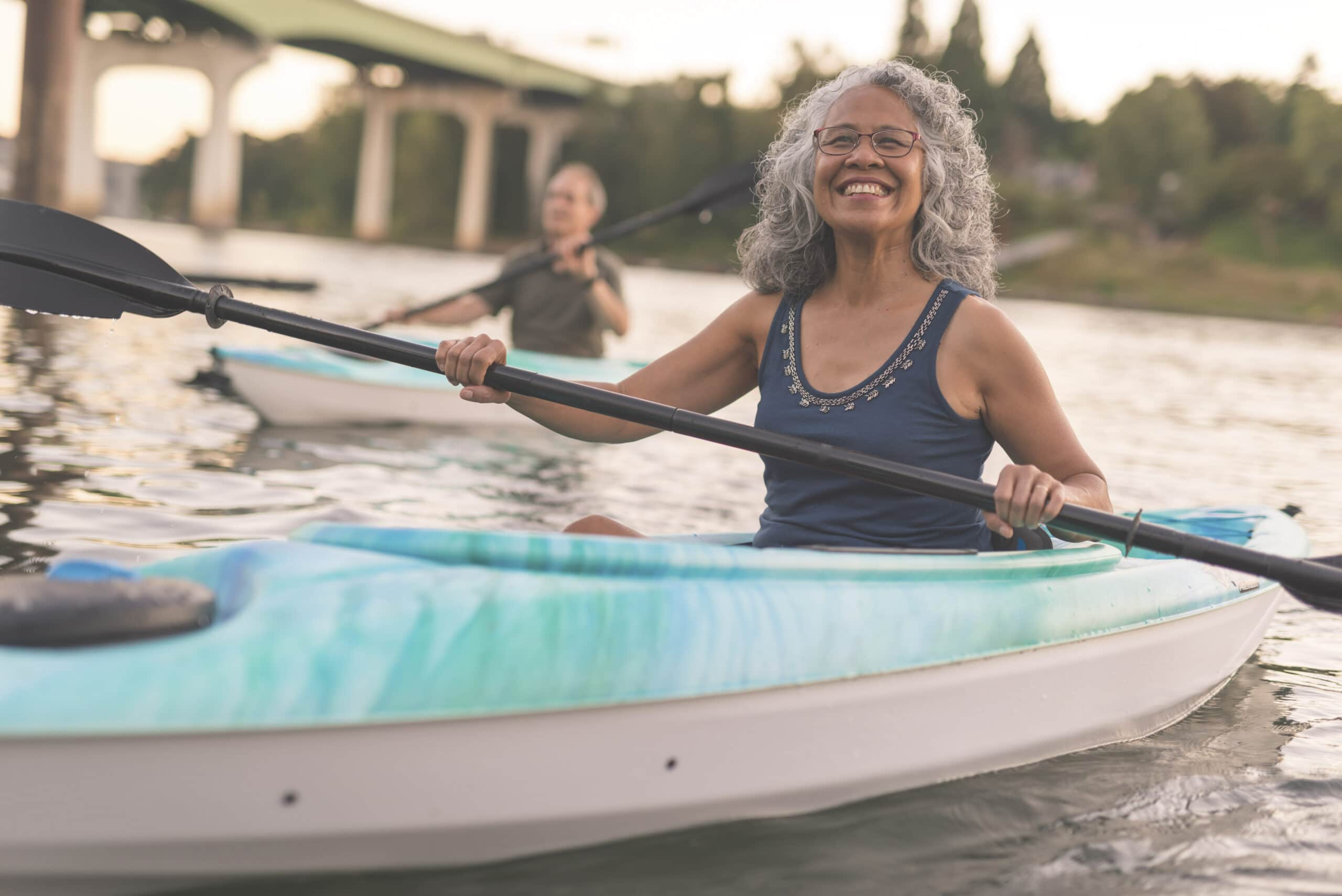 A Mixed Race Senior Couple Is Kayaking Down A River Together.