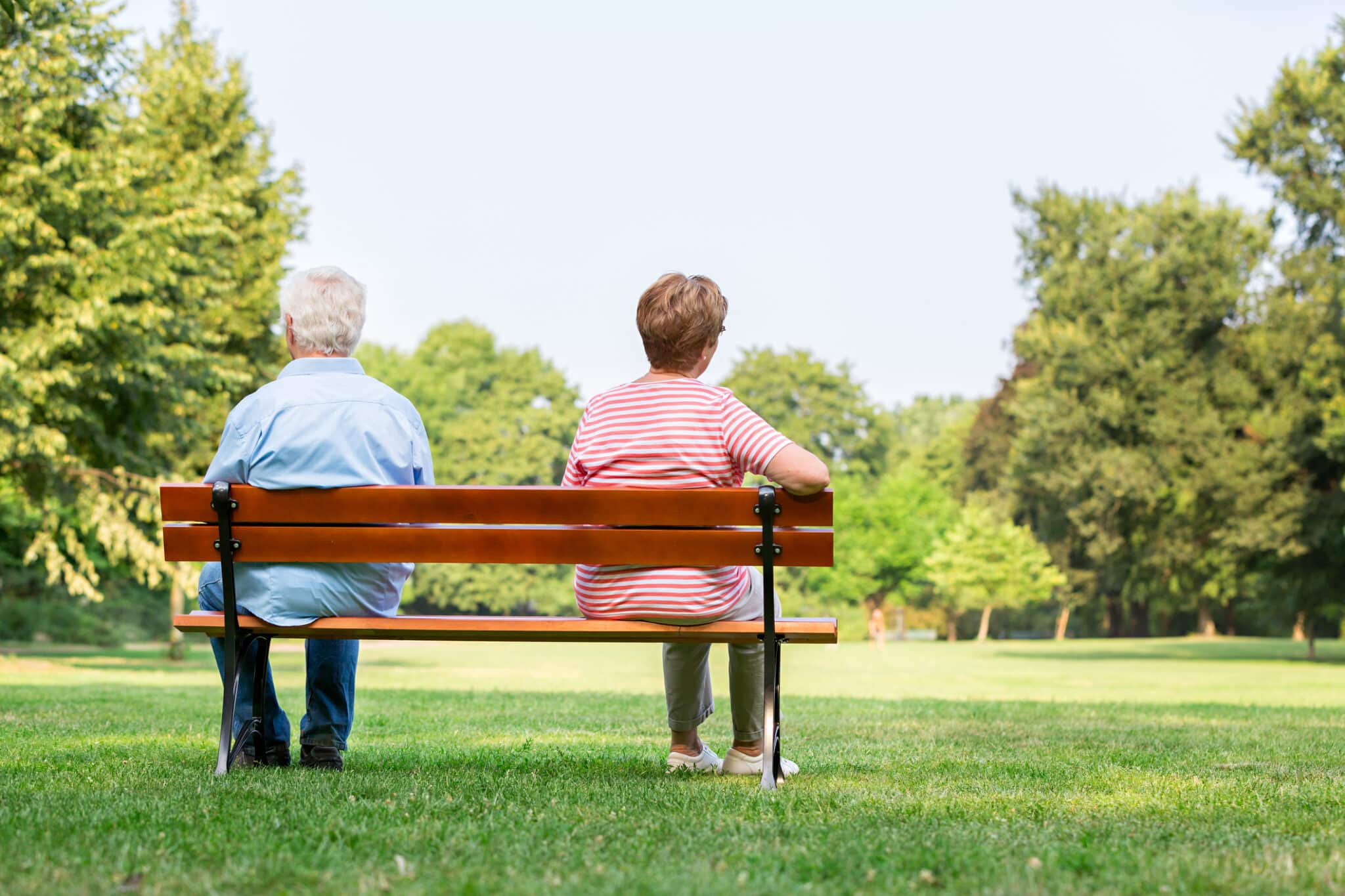 Senior Adults Sitting Apart On A Park Bench Outdoors