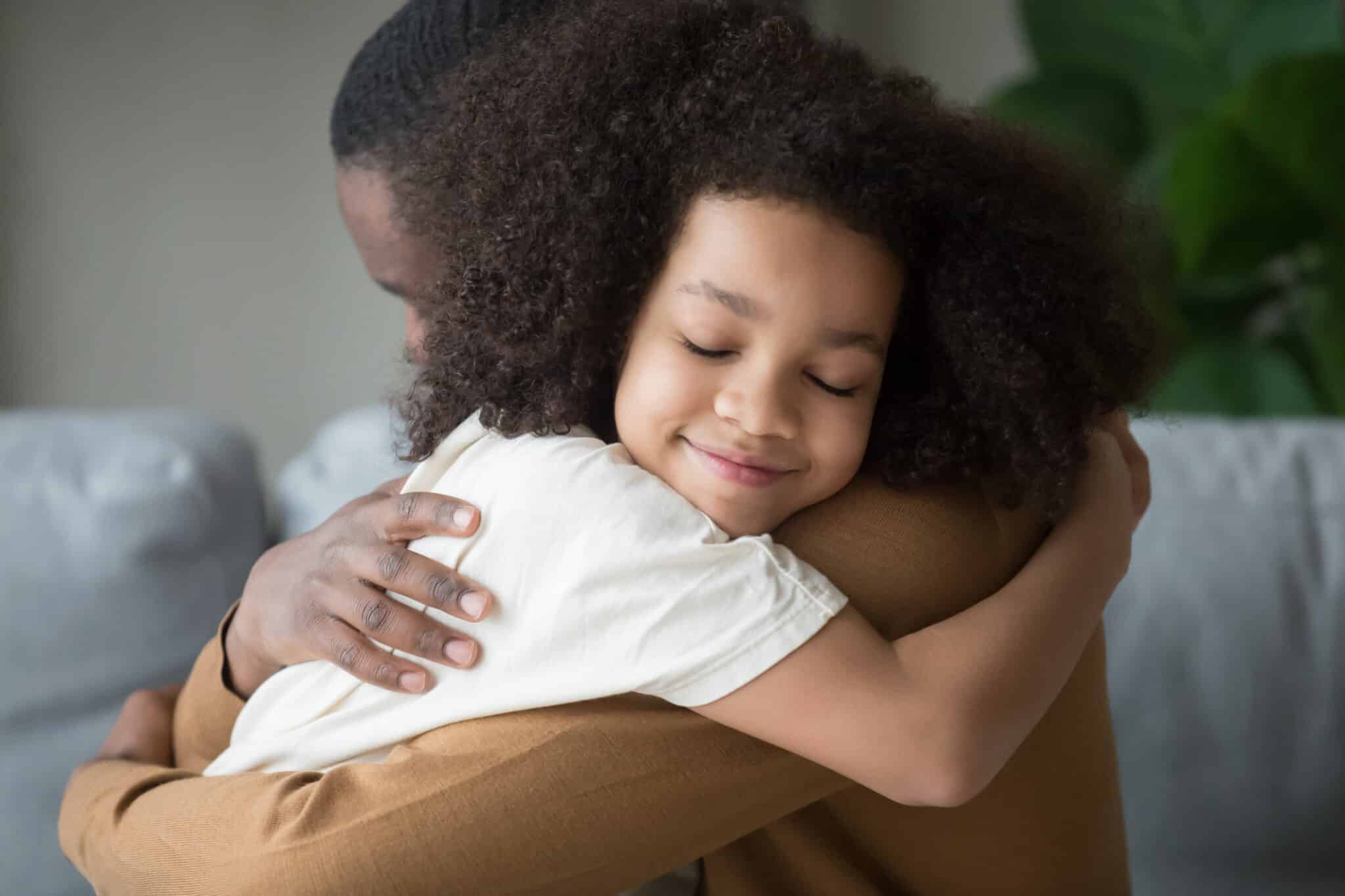 A Child Smiling With Her Eyes Closed In Her Fathers Arms