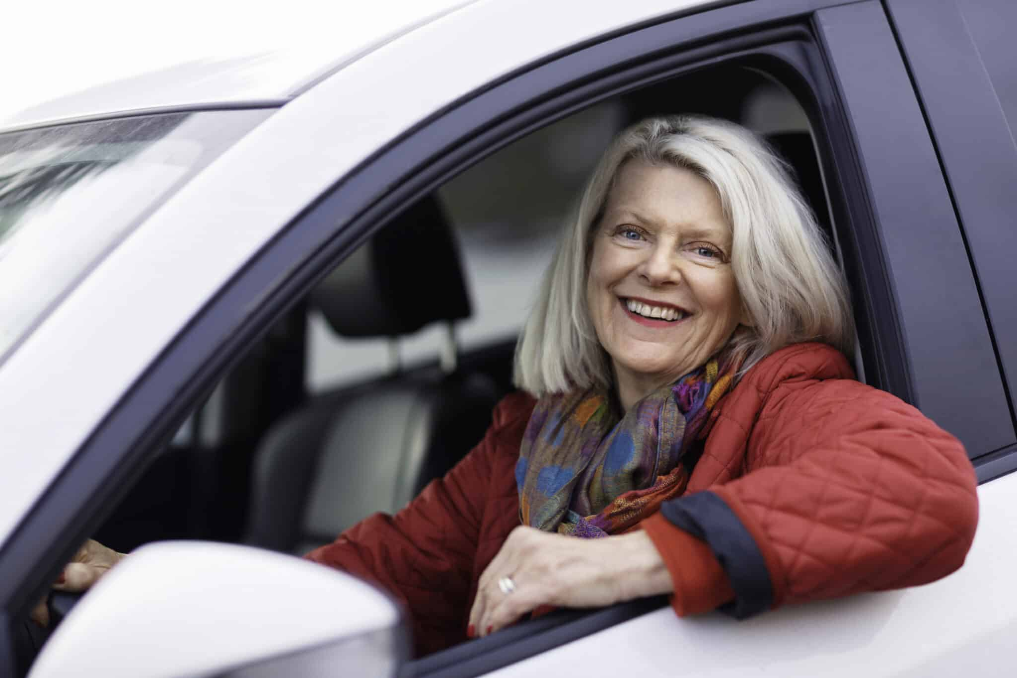 A Senior Woman Sitting In Her Car And Smiling, Facing The Camera.