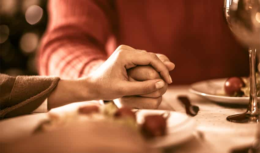 A Close-up Of A Couple Holding Hands At Dinner