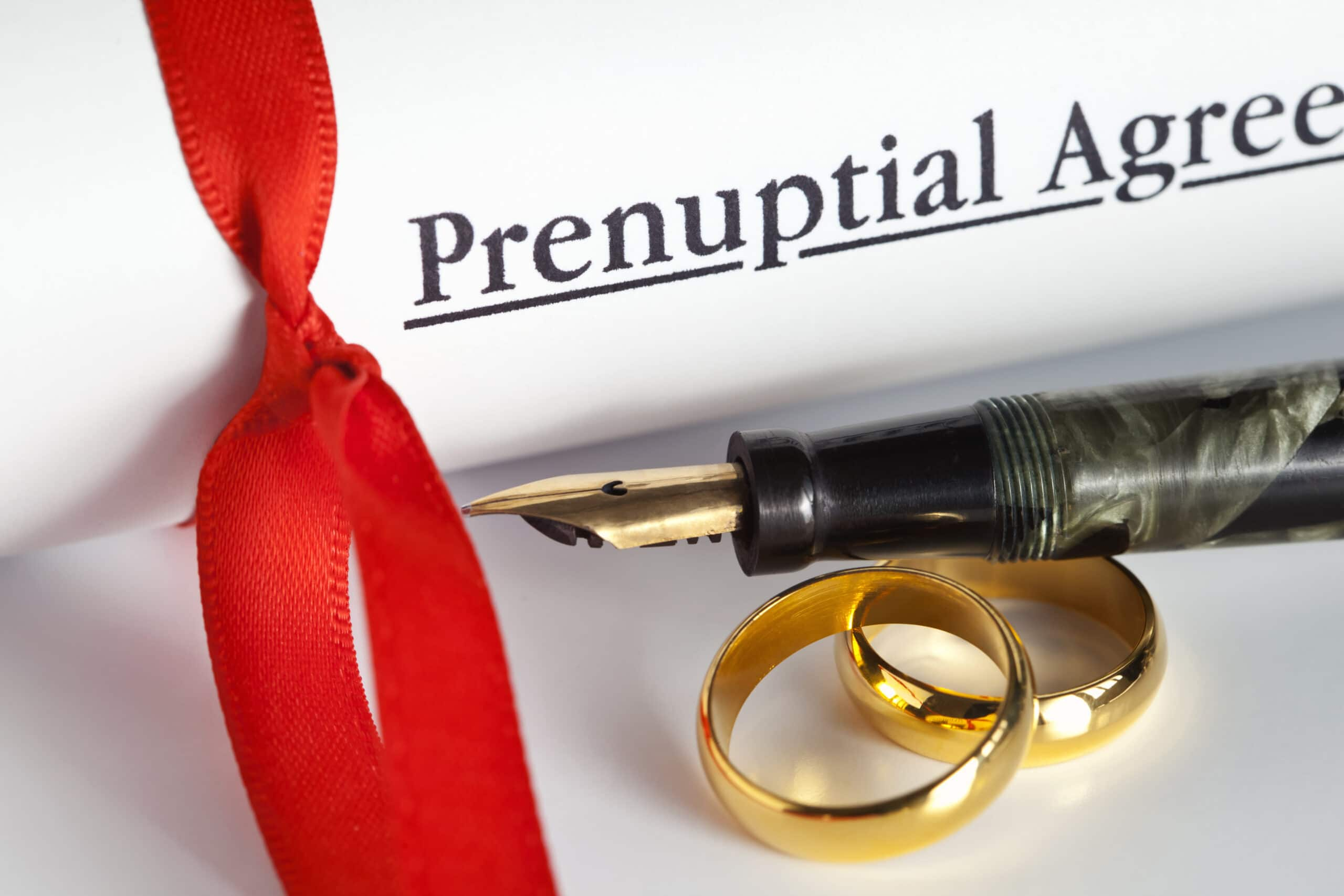 A Prenuptial Agreement Behind Two Gold Wedding Bands And A Pen