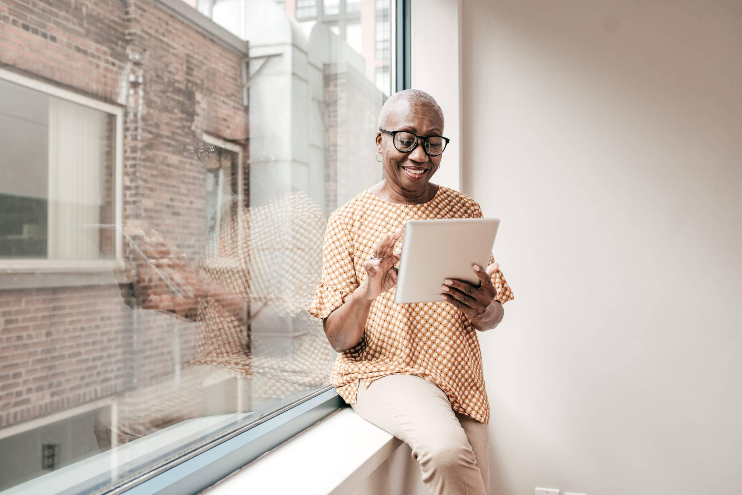 Smiling Senior Woman Reading Newspaper