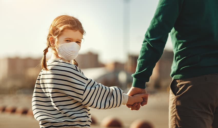 A Young, Red-haired Child Wearing A Medical Face Mask Holding Hands With Her Father